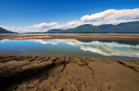 Clouds reflecting in a pool on the Fraser River in Chilliwack